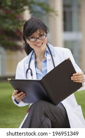 Female doctor in a white lab coat holding a binder of patient information