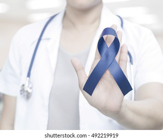 Female doctor in white uniform with royal dark navy blue ribbon awareness in hand for Acute Respiratory Distress Syndrome (ARDS),Arthritis,Chronic Fatigue Syndrome, Colitis,Colon, Colorectal Cancer