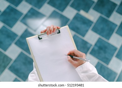 Female doctor in white uniform writing on clipboard paper patient's medical history or medicine prescription. Woman as health specialist in visit check or healthcare lifestyle concept.