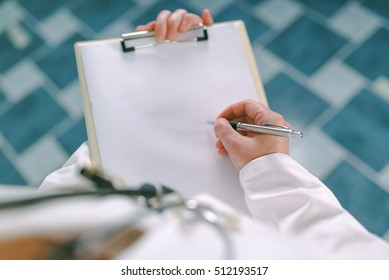 Female doctor in white uniform writing on clipboard paper as copy space for patient's medical history or medicine prescription