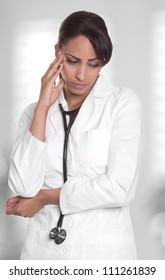 Female doctor in white is upset and lost in thought.