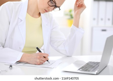 Female doctor working in medical office. Yellow t-shirt and flower at photo. Medicine concept