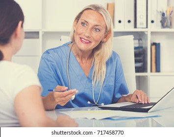 Female doctor working with patient in medical office and writing prescription