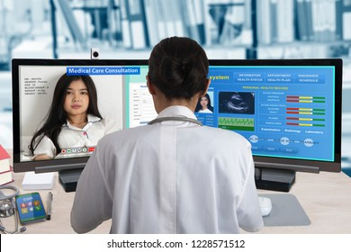 Female doctor working with two computers for distance patient consultation and searching her health information from medical record system.