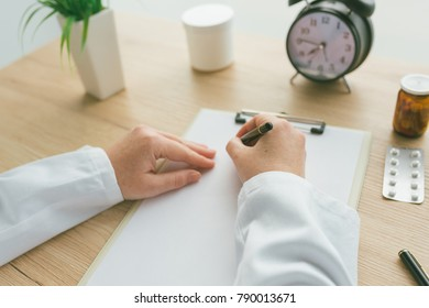 Female doctor writing notes, patient's medical history or medicine prescription on clipboard paper during medical exam in hospital office