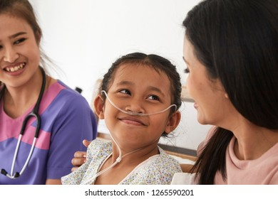 Female doctor and Young asian little patient with and mother smiling while doctor come to visit