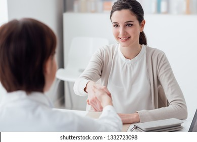 Female doctor and young smiling patient in the office, they are shaking hands