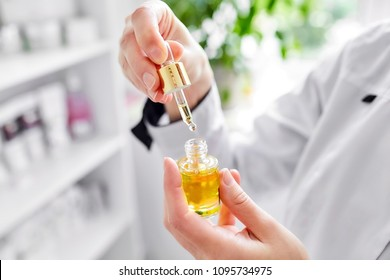 A female doctor-cosmetologist in a white coat holds a bottle of enriched argan oil. Woman with a pipette. Facial care product. Cosmetology room