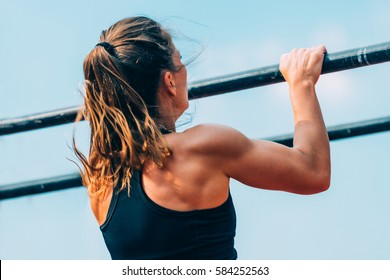 Female doing pull ups in competition