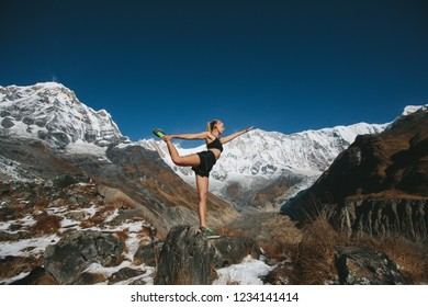 Female doing yoga exercise outdoor in beautiful snow mountains view