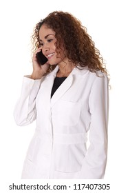 Female Dr. smiles while talking on the phone, isolated on a white background.