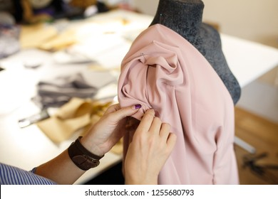 female dressmaker attach fabric to mannequin with needles. creating dress design. Tailor industry concept.