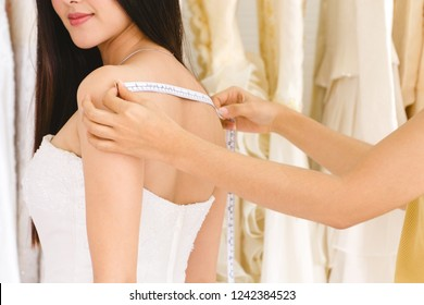 Female dressmaker measuring woman's back for wedding dress.