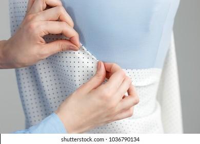 Female dressmaker working on new model tailoring dress on mannequin in studio.