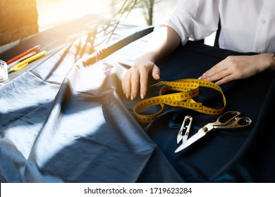Female dressmaker's hands lie on a cut table next to scissors, a centimeter tape, a clipper for carving and pencils.