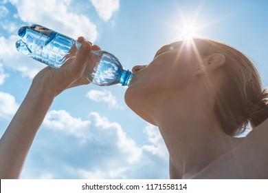 Female drinking bottle of water on a hot summer day.