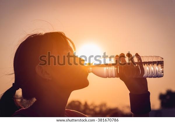 Female drinking a bottle of water silhouette.