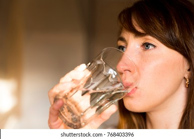 Female drinking from a glass of water. Health care concept photo, lifestyle, close up