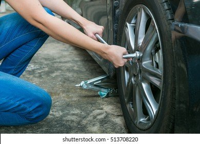 Female driver changing tyre on her broken car.