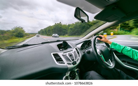 A female driver driving a car along a busy road on an English single carriageway on a cloudy overcaste day.