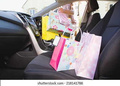 Female Driver Getting Into Car With Shopping Bags