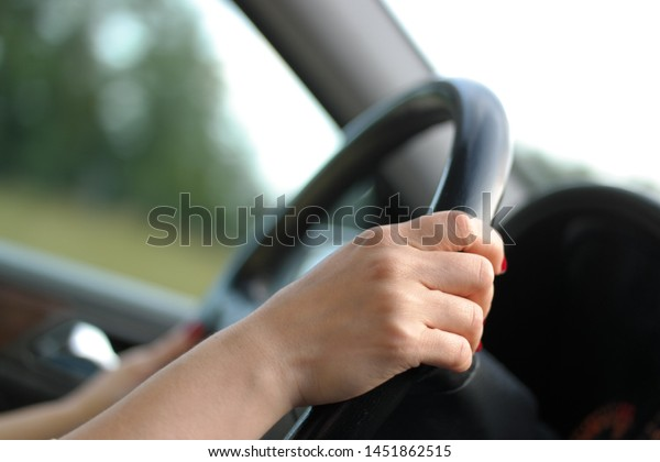 female driver is holding steering wheel