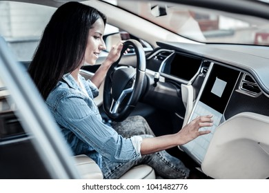 Female driver. Nice attractive young woman sitting behind the wheel and pressing the button while starting her car