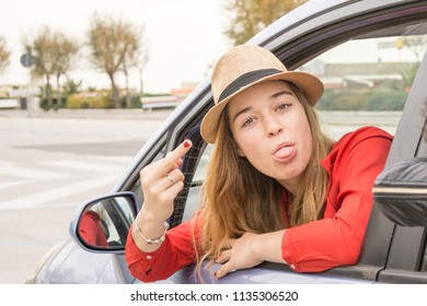 female driver showing middle finger in and obscene gesture or vulgarity or funny . concept of offensive gesture while driving car.