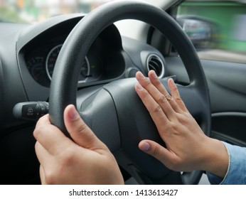 Female driver steering a car and press car horn, honking soung to warn other people in traffic