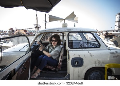 Female driver at the wheel of an old car