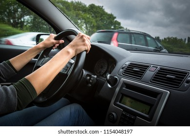 Female driver's hands driving a car on a highway (color toned image; shallow DOF)