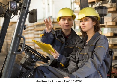 Female drivers wearing in gray uniform and yellow helmets, working in cargo truck. One woman showing to another by hand at side. Colleagues with yellow folder pointing at production, discussing job.