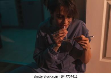 Drogensüchtige Frauen, die im Dunkeln auf dem Küchenboden sitzen und ihre nächste intravenöse Heroindosis mit Spritze und Löffel vorbereiten; Drogenabhängigkeit