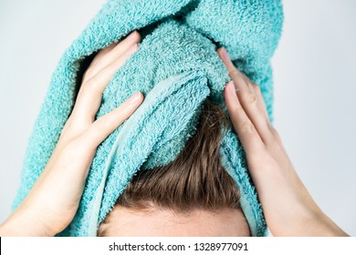 Female drying her hair with towel. Close-up of woman using bath towel for manual hair drying