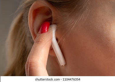 female ear with bluetooth earphone and finger closeup