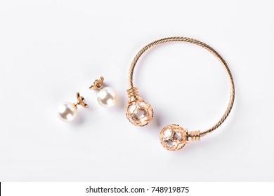 Female earings and bracelet on white background. Earings with pearl and bangle, white background. Woman bijouterie isolated on white background.