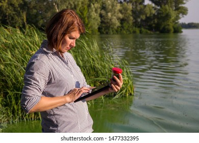 female ecologist entering information on green algae taken in river on tablet