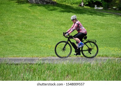 Female electric bicycle rider on rails to trail path along river.