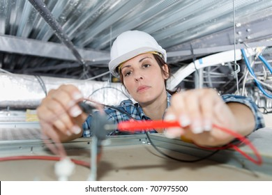 female electrician fixing ceiling wiring