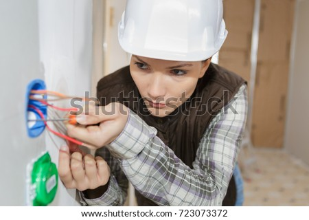 female electrician fixing electric