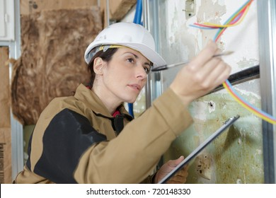 female electrician inspecting the cables