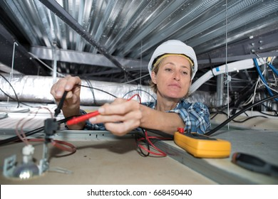 Female electrician testing charge to spotlight
