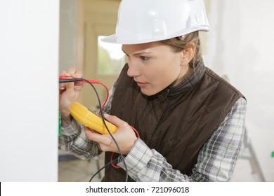female electrician testing a wall socket