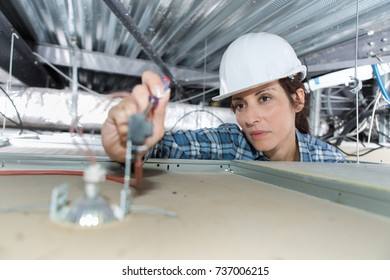 Female electrician working on spotlamp from above