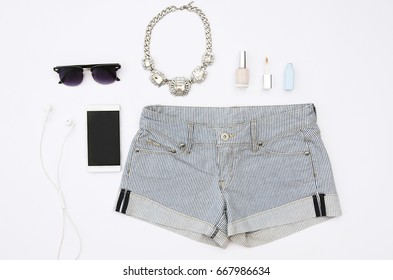 Female elegant stuff on white background. Top view of mobile, headphones, sunglasses, necklace, makeup and shorts.