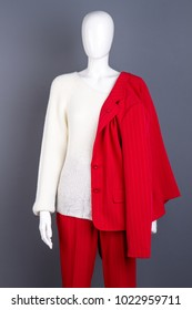Female elegant suit and white sweater. Female mannequin with red blazer, trousers and white pullover on grey background. Boutique of feminine outfit.