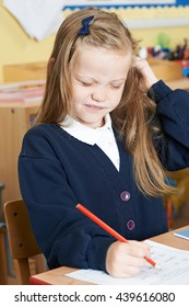 Female Elementary Pupil Suffering From Head Lice In Classroom