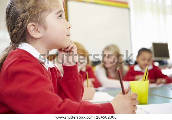 Female Elementary Pupil Working At Desk