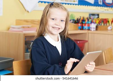 Female Elementary School Pupil Using Digital Tablet In Class