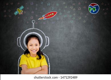 Female elementary school student smiling at the camera while imagining being an astronaut